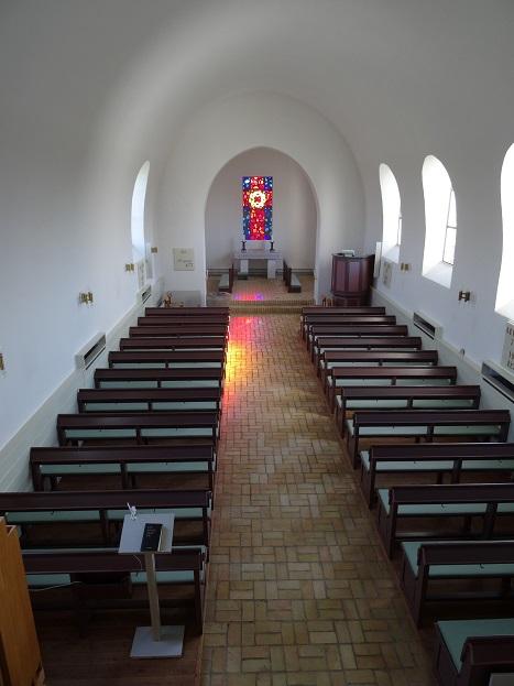 Aunsø Kirke indvendig fotograferet fra pulpituret. Over alteret se Svend Havsteen Mikkelsens glasmosaik visende korset med tornekransen indsat i dettes skæringspunkt. Foto: Flemming Paulsen