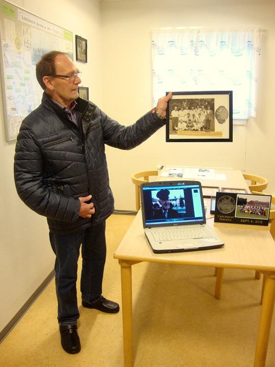 """John Gøttsche viser et billede frem, hvor han selv er med. John Gøttsche spillede på et af Svebølle Boldklubs ungdomshold, der i 1959 blev Danmarksmestre ved et fodboldstævne afholdt af DBU i Vingsted Bemærk, at """"Verdens ældste taxavognmand"""", Jens Chr. Petersen er kommet med på det lille skærmbillede. - Foto: F.P."""